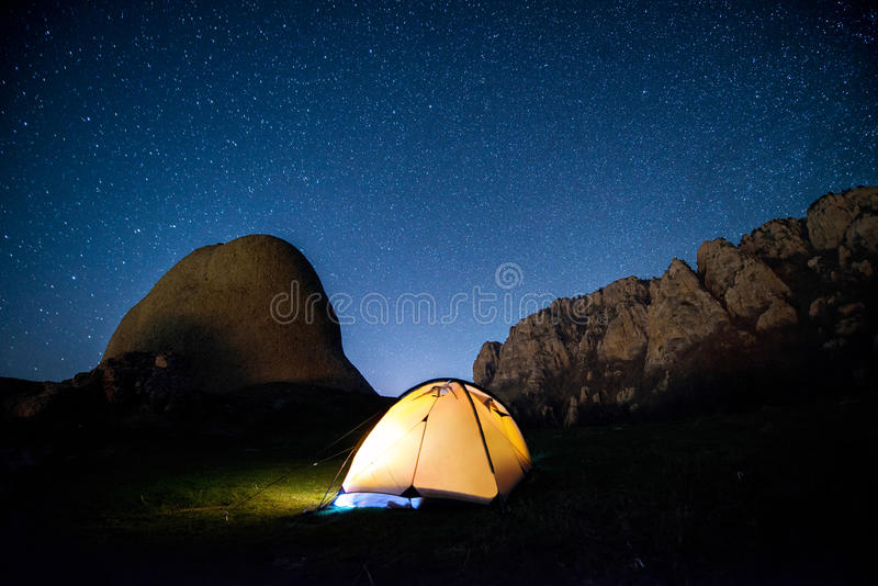 Glowing camping tent in the mountains under a starry sky. Crimea, Demerdzhi. Long exposure - 43 seconds, ISO 640, f/2.8, 14mm. March 2017 royalty free stock photo