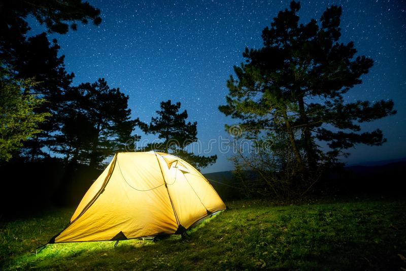 Glowing camping tent in the night mountain forest under a starry sky royalty free stock photos