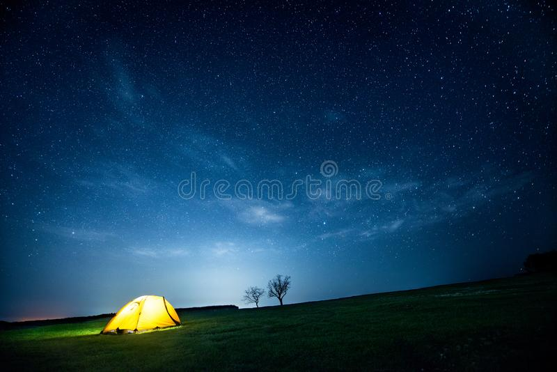 Glowing camping tent in the night mountains under a starry sky stock photography