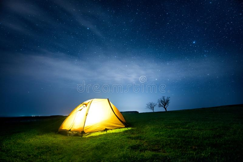 Glowing camping tent in the night mountains under a starry sky royalty free stock photos