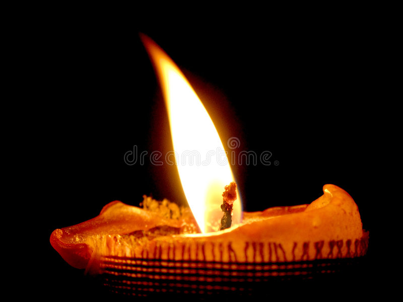 Glowing candle. Isolated glowing candle with oblique flame. Black background royalty free stock photos