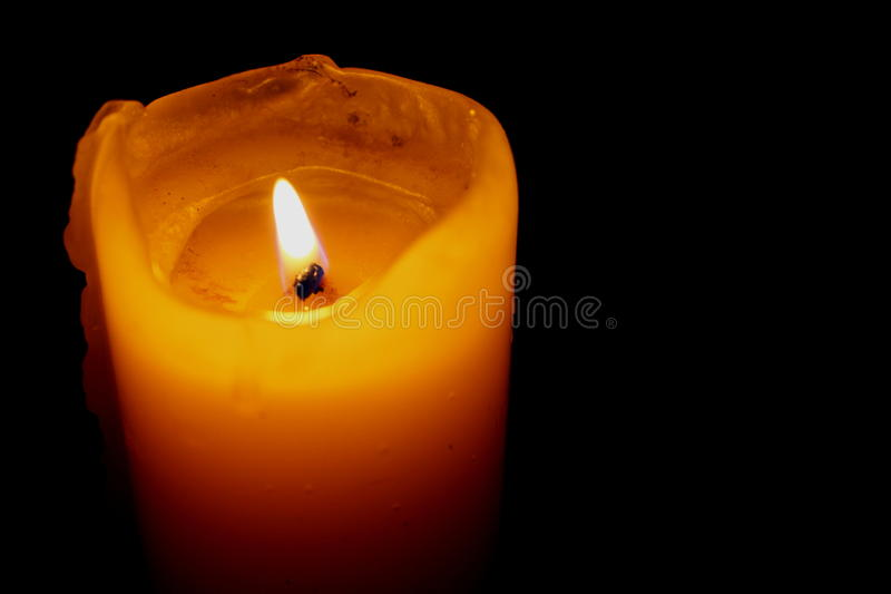 Glowing Candle Against a Black Background. A lit, glowing candle against a dark, black background stock photography