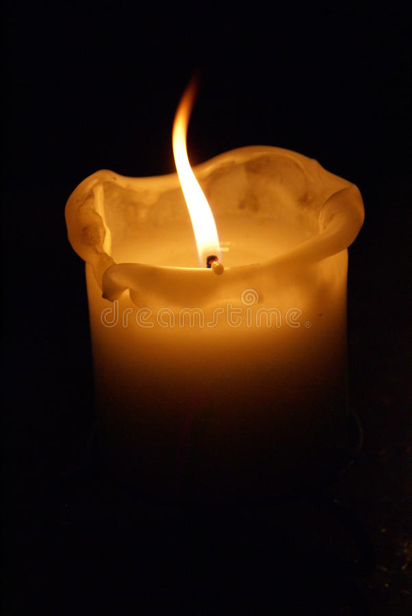 Glowing Candle. Home decoration of a glowing white candle at night royalty free stock images