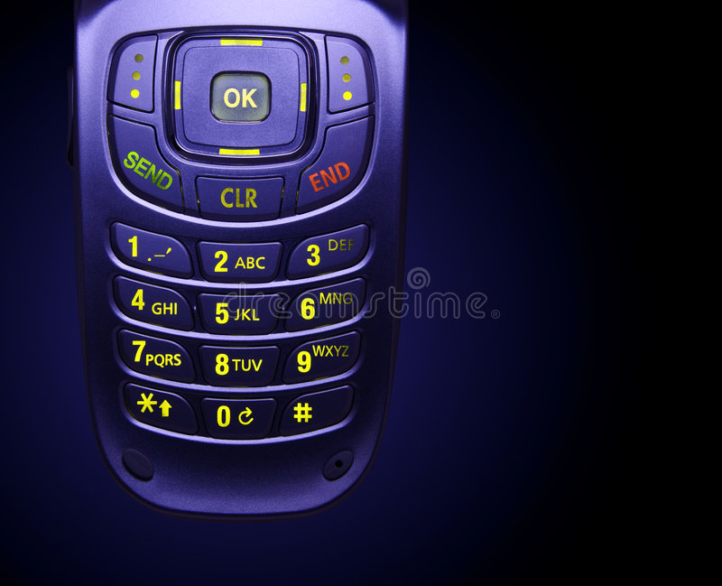 Glowing Cell Phone Keypad. Close-up of a cellular phone keypad glowing on a black background stock photography