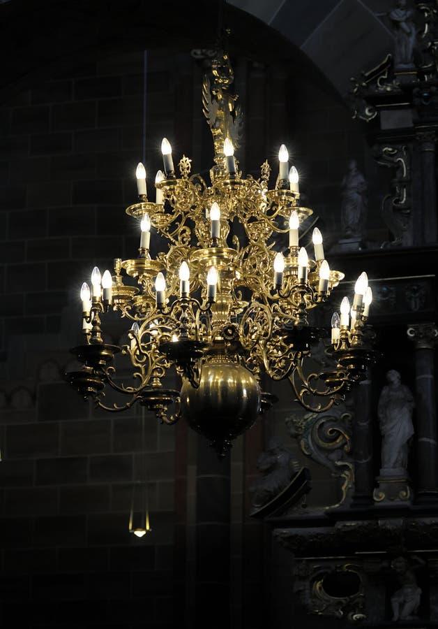 Glowing chandelier hanging in darkness stock photo