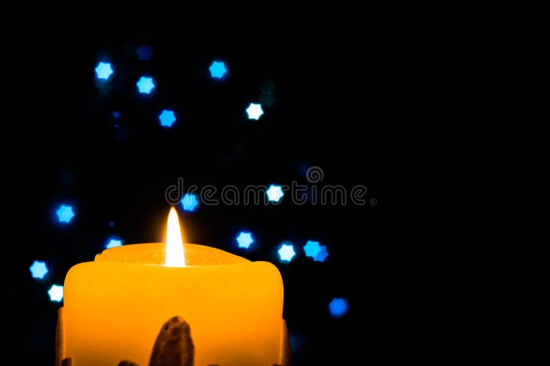 Glowing Christmas candle with blue Christmas lights. In the background stock photo