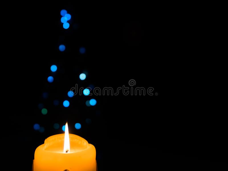 Glowing Christmas candle with blue Christmas lights. Glowing Christmas candle with blue Christmas lights in shape of Christmas tree in the background royalty free stock images