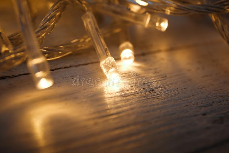 Glowing Christmas lights on white wooden background. Closeup royalty free stock photo