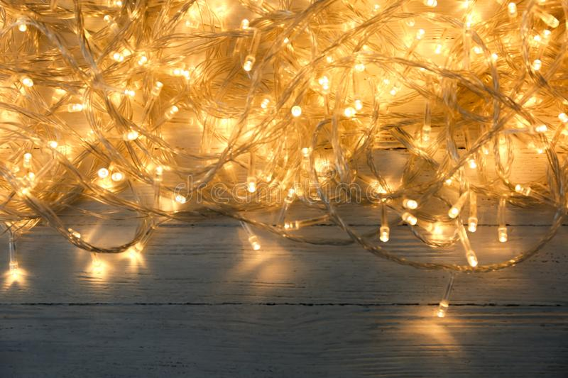 Glowing Christmas lights on white wooden background. Top view stock photos