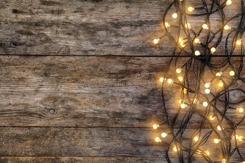 Glowing Christmas lights on wooden background. Top view royalty free stock photography