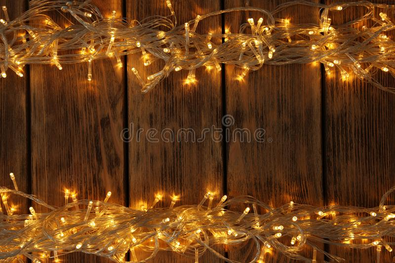 Glowing Christmas lights on wooden background. Space for text. Glowing Christmas lights on wooden background, top view. Space for text royalty free stock image