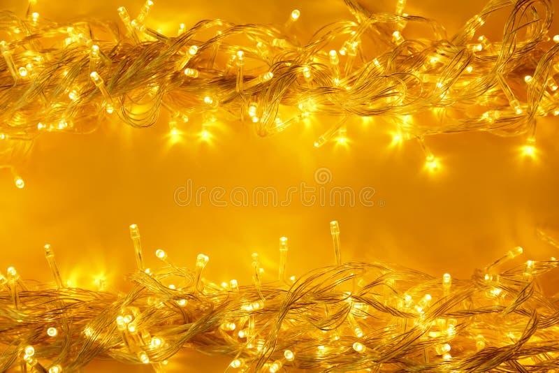 Glowing Christmas lights on yellow background. Space for text. Glowing Christmas lights on yellow background, top view. Space for text stock images