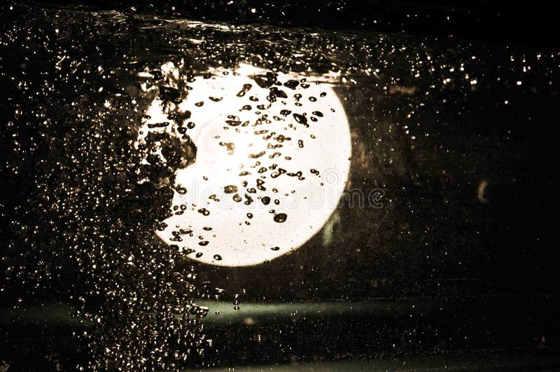 A glowing circle under the water, lamp standing behind the water tank filled with water royalty free stock images