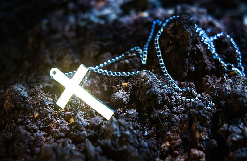 Glowing cross on the chain. Mystery dark background stock photos