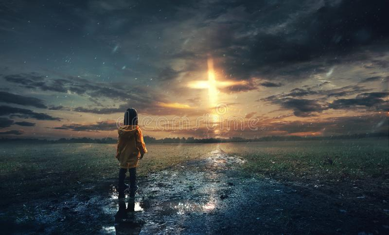Glowing cross in the rain. A little girl stands in the rain with a glowing cross in the sky stock photo