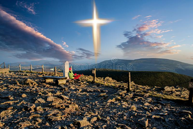 Glowing cross . Walk to the cross. Glowing cross . All alone . Seclusion renunciation of the world . Faith in God. Prayer at the top of the mountain stock photos