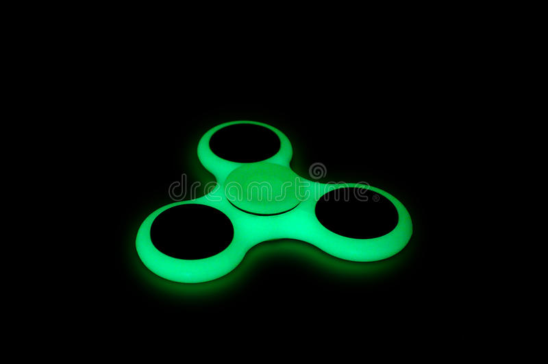 Glowing in the dark fidget spinner. Green glowing in the dark fidget spinner on black background royalty free stock images