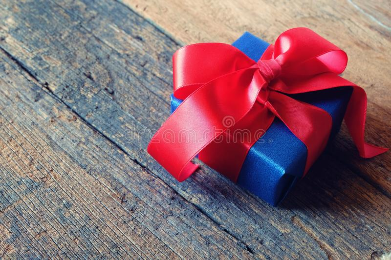 Glowing deep blue with red ribbon gift box on vintage wooden table. A present with love concept. Backdrop for Valentine& x27;s day royalty free stock images