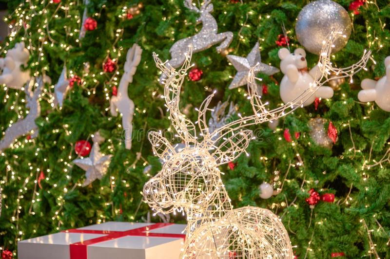 Glowing deer with light decoration with toy on christmas tree stock photography