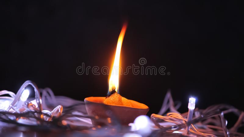 Glowing Diya in the middle with black Dark background and led lights around on the ground floor. Glowing Diya in the middle with black Dark background and led royalty free stock photography