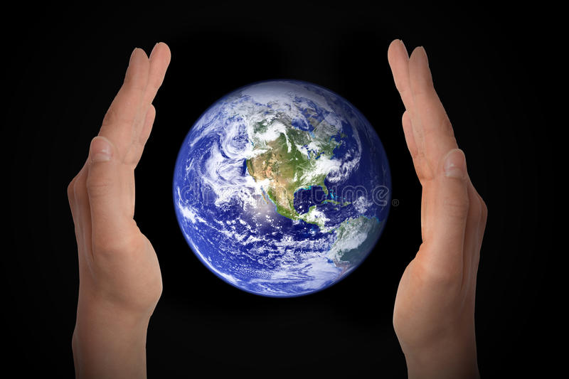 Glowing earth globe in hands on black, environment concept - elements of this image furnished by NASA royalty free stock photography
