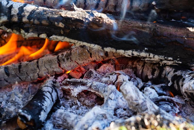 Glowing embers in the ash with log in smoke, macro royalty free stock photos