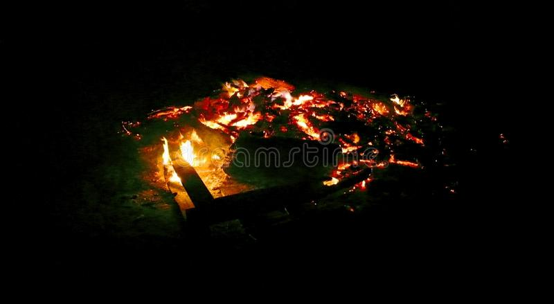 Glowing embers version b. A camp fire glowing outdoors of an evening.  End of a long day royalty free stock images