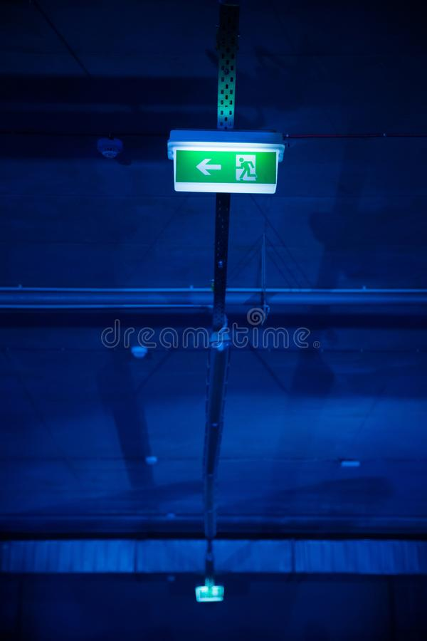 Glowing exit sign symbol ant the underground parking garage stock photography
