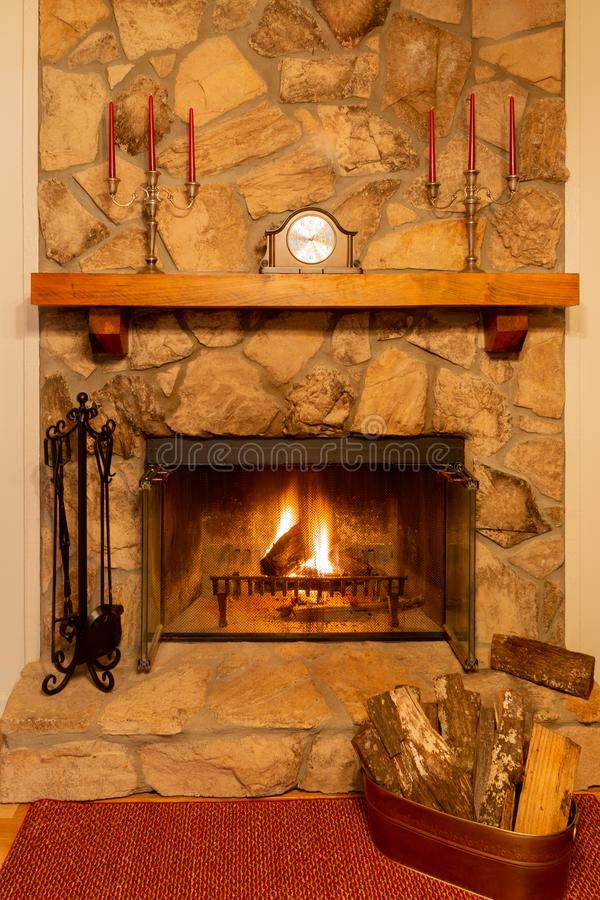 A warm fire in a beautiful stone fireplace with clock and candelabras on the mantle. A glowing fire in a beautiful stone fireplace with clock and candelabras on royalty free stock image