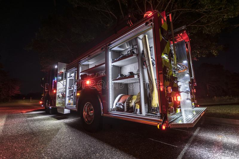 Glowing fire truck at night. Fire truck with all compartments open and lights on illuminating the ground below it stock image