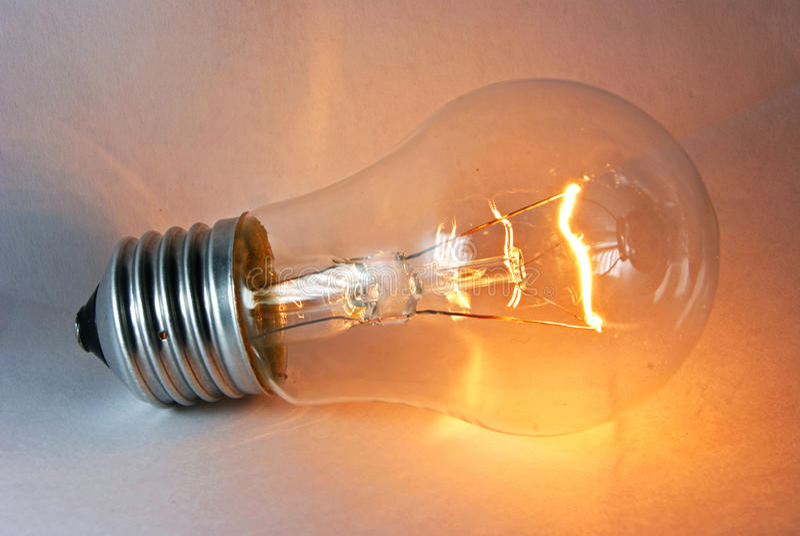 Glowing flashing light bulb lamp laying royalty free stock images