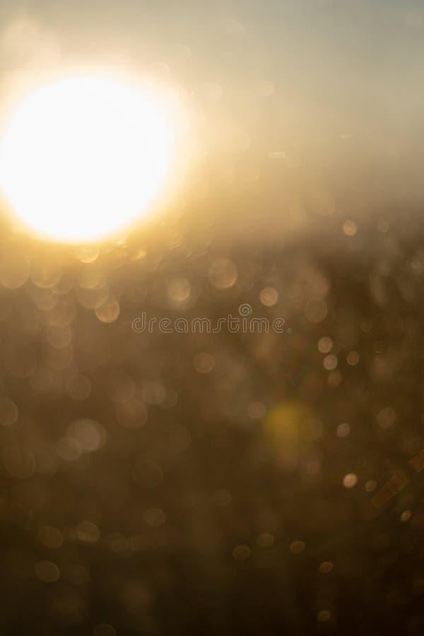 Glowing through glass of water orange sun during sunset, close-up, defocused. Glowing through glass with drops of water orange sun during sunset, close-up stock photo