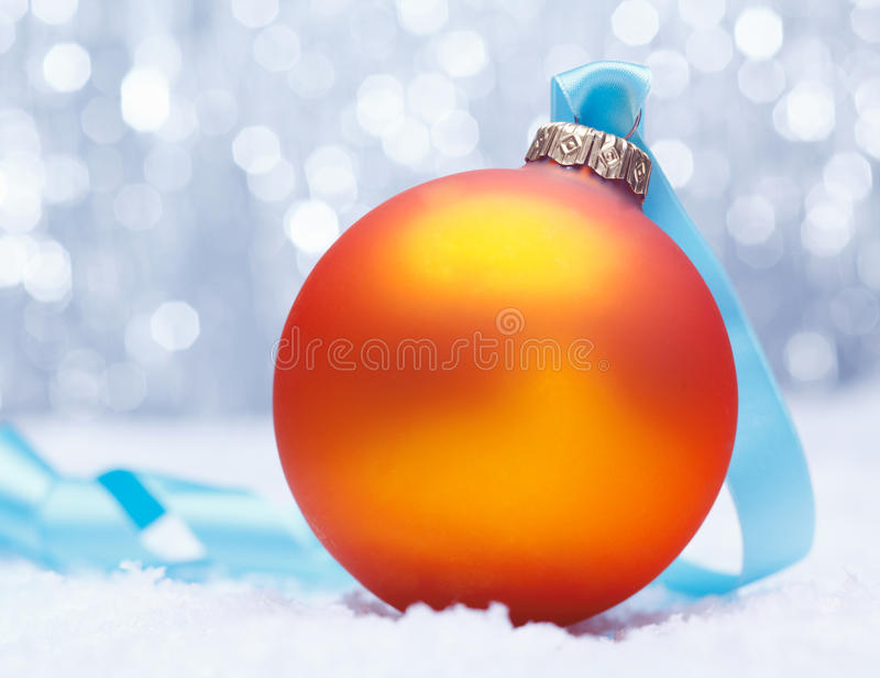 Glowing golden orange Xmas bauble royalty free stock photography