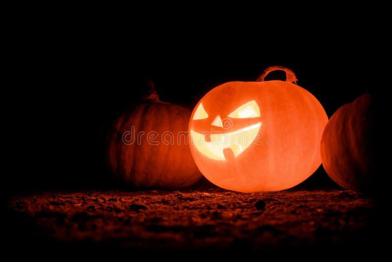 Glowing Halloween pumpkin on a black background. Creepy pumpkin. stock photos