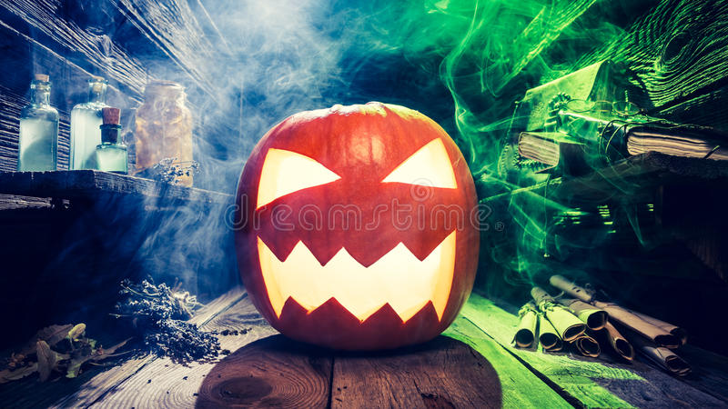 Glowing Halloween pumpkin in witcher cottage stock images