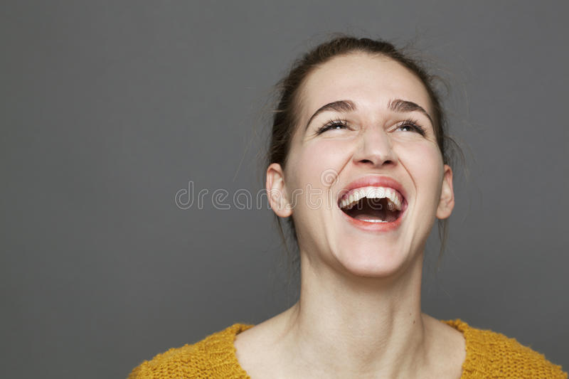 Glowing happiness concept for beautiful girl bursting out laughing stock photo