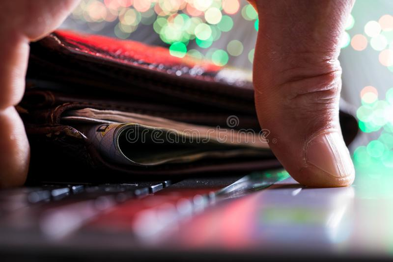 Glowing high speed internet optical fibres, opened wallet on computer keyboard, caucasian man hand on keyboard royalty free stock photo