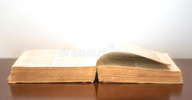 Glowing historic book. Glowing warm light originating from the pages of an old book. The book used for this image is a dictionary royalty free stock photo