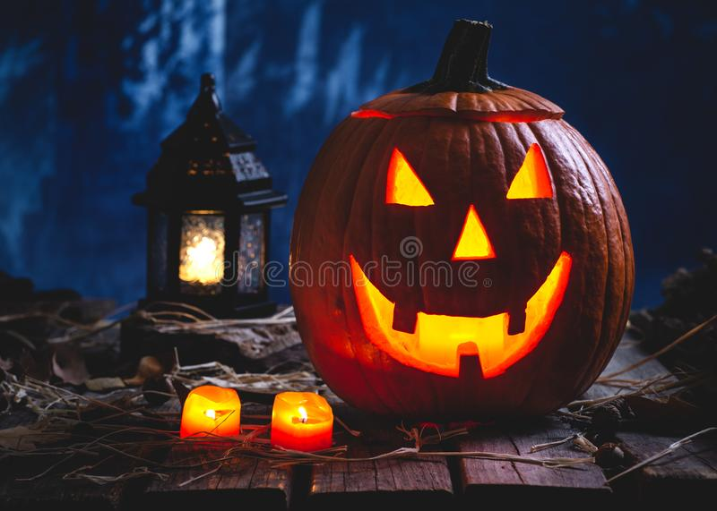 Glowing Jack-O-Lantern With Burning Candles and Lantern. On a dark spooky background royalty free stock images