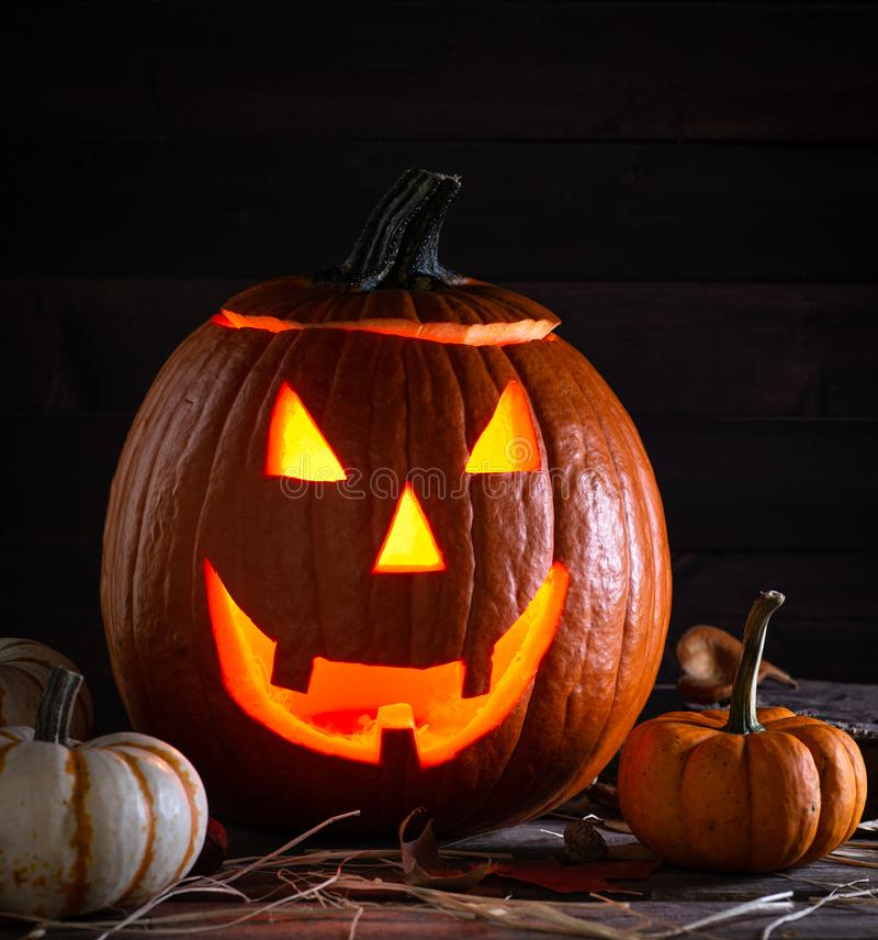 Glowing Jack O Lantern and and Pumpkins. Glowing Jack-O-Lantern with mini pumpkins on a rustic wooden surface and background stock images