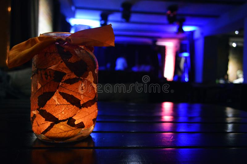 A glowing jar with leaves and a candle inside. Cozy evening atmosphere stock photos