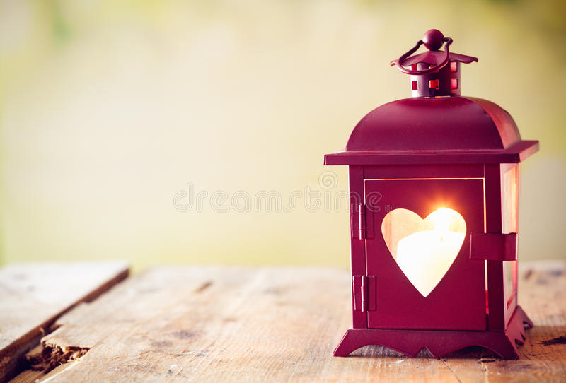 Glowing lantern with a heart. Decorative red metal lantern with a heart cutout lit by a glowing candle with copyspace for Valentines or Christmas royalty free stock photos