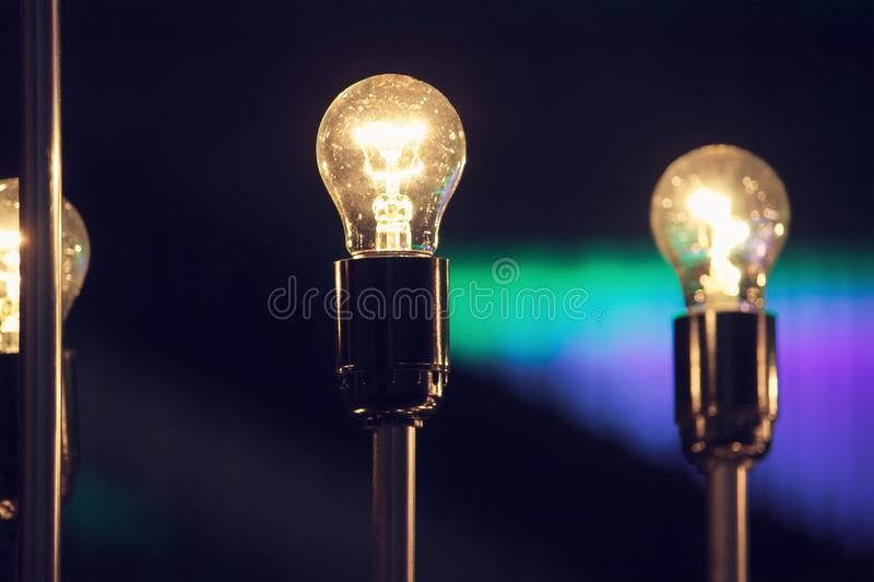 Glowing light bulb against blue wall background. Glowing white light bulb against blue wall background royalty free stock photos