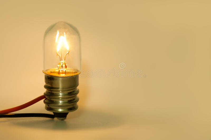 Glowing light bulb. Retro style filament lightbulb with electric wires on yellow background. Macro view, shallow depth. Vintage light bulb. Retro style filament stock photography