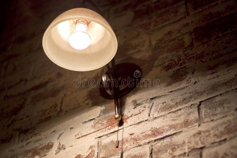 Glowing light bulb on wall stock photos
