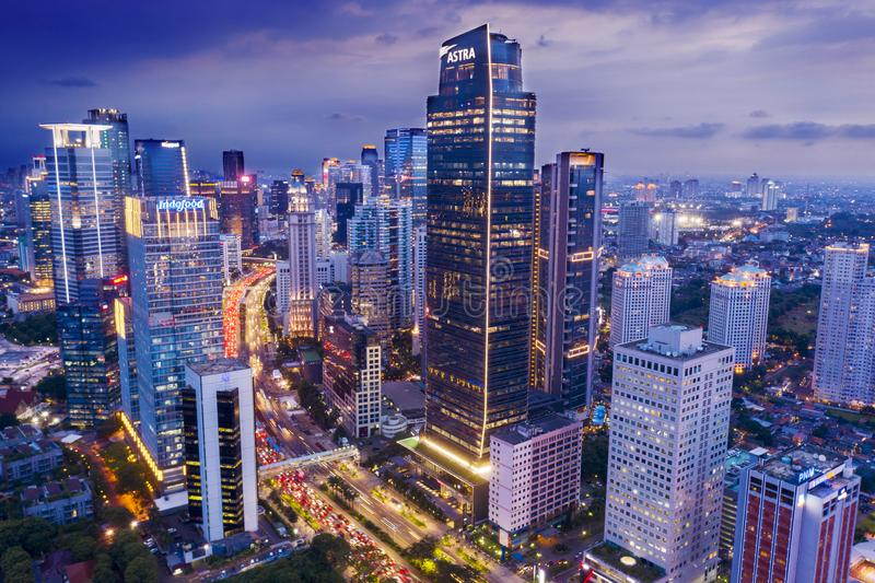 Glowing light skyscrapers with traffic at evening. JAKARTA - Indonesia. March 20, 2019: Glowing light skyscrapers with traffic road at evening time in Jakarta royalty free stock photos