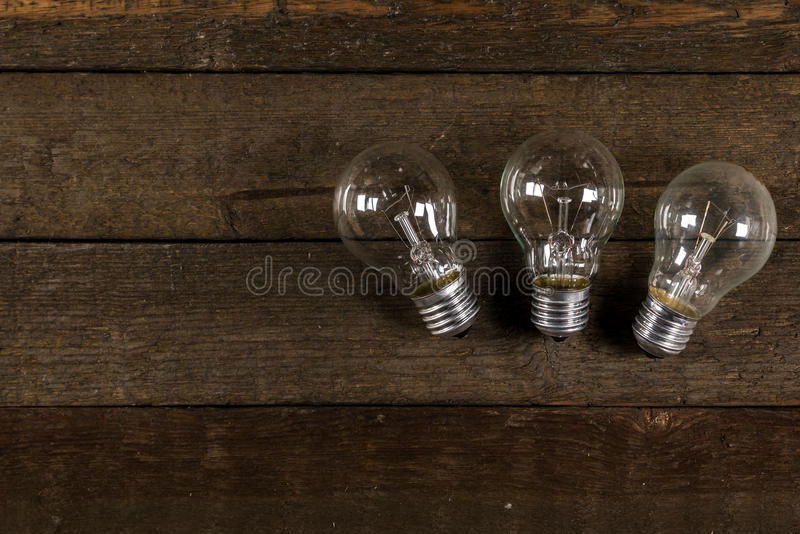 Glowing lightbulbs. On wooden background royalty free stock photos