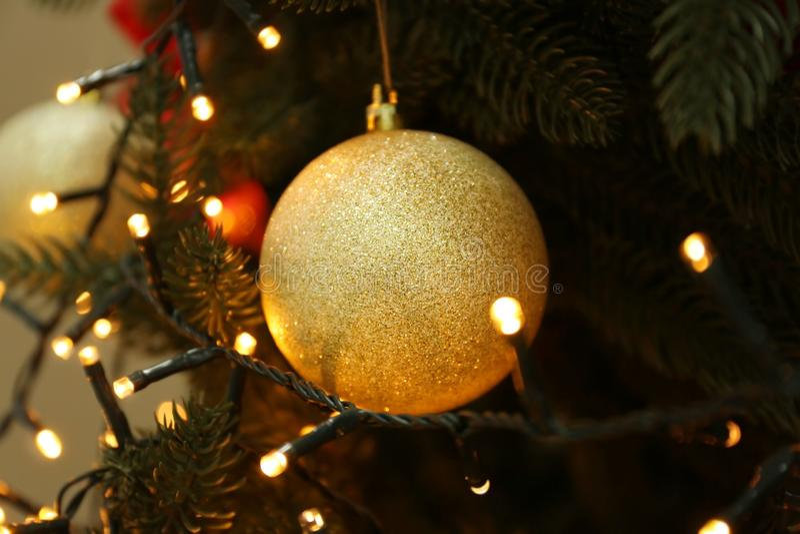 Glowing lights and Christmas ball on fir tree stock image