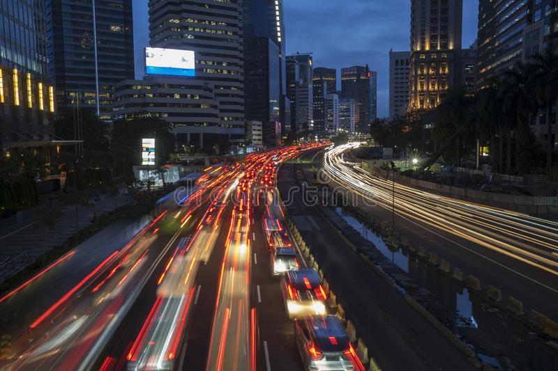 Glowing lights from hectic traffic on the road. JAKARTA - Indonesia. March 20, 2019: Drone view of glowing lights from hectic traffic on the road at dusk time in stock image