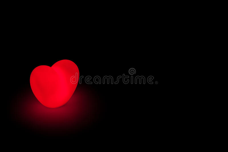 Glowing love heart on black background stock photography